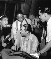 Sister Rosetta Tharpe with Duke Ellington (at piano) and Cab Calloway, with trombonist J.C. Higginbotham ad trumpeter Hot Lips Page looking over the Duke's shoulder, taken in 1939.