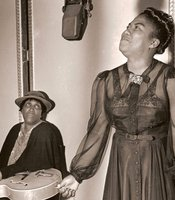 Sister Rosetta Tharpe recording at Decca Records with her mother Katie Bell holding her guitar in 1941.