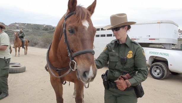Border Patrol Agent Monica Slack and her assigned mount, Shamus, stand in front of the Playas de Tijuana on the U.S. side of the border.