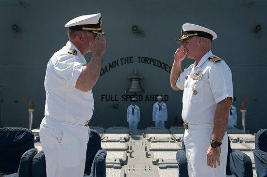 Capt. Timothy Kott, right, relieves Capt. Thomas Halvorson, left, as commanding officer of the Ticonderoga-class guided-missile cruiser USS Mobile Bay (CG 53) during an at sea change of command ceremony.
