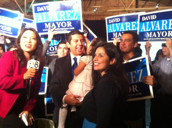 David Alvarez holding his daughter in front of supporters.