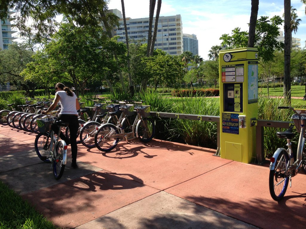 A woman picks up a DecoBike bicycle at a bike sharing station in Miami.