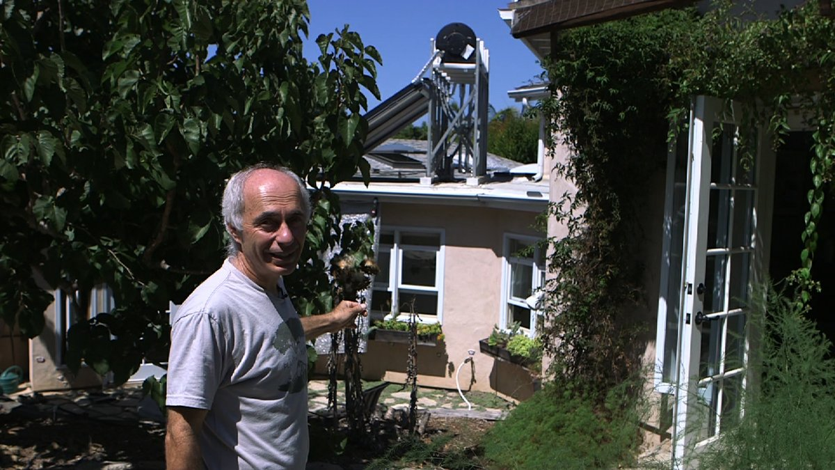 Dadla Ponizil shows the solar water heater on the roof of his Encinitas home.