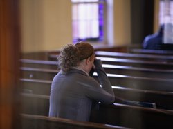 A woman prays at Saint Rose of Lima Roman Catholic Church in Newtown, Conn., on Saturday.