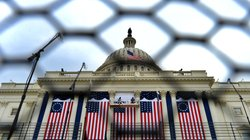 Workers seen through a fence adjust American flags on the Capitol during preparations Thursday for the inauguration.