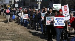 Abortion opponents march to a rally at the Kansas Statehouse in Topeka, Kan., on the 40th anniversary of