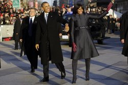 President Obama and first lady Michelle Obama walk in the inauguration parade near the White House. The first lady chose a jacket by designer Thom Browne.
