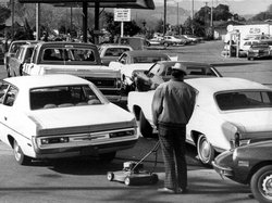 Drivers and a man pushing a lawnmower lined up at gas station in San Jose, Calif. on March 15, 1974.