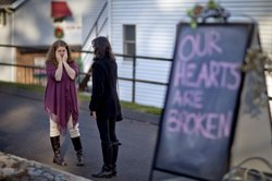 Shop owners Tamara Doherty, left, and Jackie Gaudet, right, meet outside their stores for the first time since being neighbors, just down the road from Sandy Hook Elementary School in Newtown, Conn.