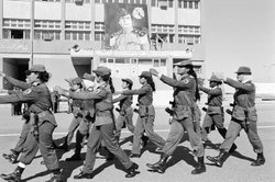 Female soldiers with AK-47 rifles and bayonets march on the parade grounds at the Women's Military Academy in Tripoli, Libya, on Jan. 18, 1986. At rear is a portrait of of Libyan ruler Moammar Gadhafi.
