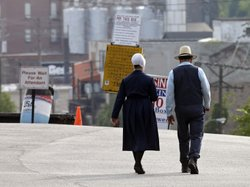 An Amish man and woman walk through a parking lot after leaving the U.S. courthouse in Cleveland in September. Sixteen members of an Amish group in Bergholz, Ohio, led by Sam Mullet, were found guilty of attacks targeting Amish bishop and shearing their hair and beards.