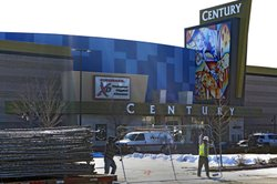 Workers dismantle the fence around the remodeled Century theater in Aurora, Colo., in preparation for the cinema's reopening Thursday. The theater's owner sent 2,000 invitations to the private event, being held for victims' families and first responders.