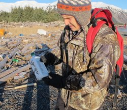 Chris Pallister examines a bottle on Montague Island of what he believes could be a household chemical item.