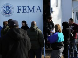 Residents wait for information from FEMA in the Rockaway neighborhood of Queens, N.Y. Superstorm Sandy washed away a large section of the iconic boardwalk here on Nov. 2.