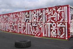Los Angeles artist RETNA developed his own alphabet from gang writing and calligraphy. The top line on this RETNA mural reads &quot;sacred dance of memories.&quot;