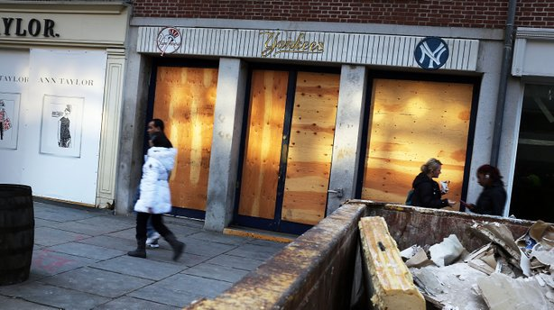 People walk past a closed business affected by Hurricane Sandy in the heavily damaged South Street Seaport in New York City on Dec. 3.
