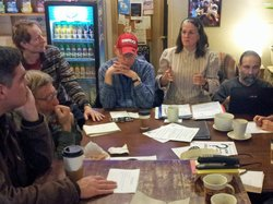 Members of the Saratoga Peace Alliance discuss plans for a street action they plan to stage at the city&#39;s upcoming gun show.