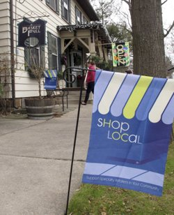 "A flag urges customers to shop locally near a store in Boalsburg, Pa., on Friday. Owners of small stores hope to get a boost from ""Small Business Saturday."""