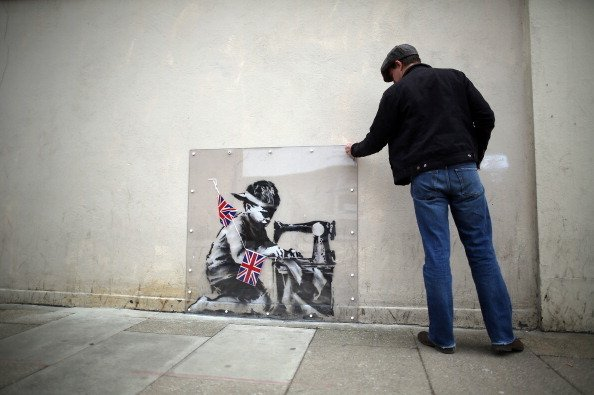 A man inspects a plastic cover placed over an artwork attributed to Banksy in London. The stencilled image depicts a poor child making Union Jack flags on a sewing machine and is located on the wall of a Poundland discount shop in the Wood Green area of north London.