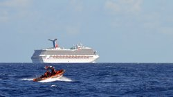 The Coast Guard patrols near the cruise ship Carnival Triumph in the Gulf of Mexico on Monday. The Carnival Triumph lost propulsion power after an engine room fire a day earlier.