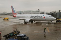 An American Airlines 737-800 aircraft featuring the company's new logo sits at a gate at Chicago's O'Hare Airport in January. American's merger with US Airways would create the largest U.S. airline.