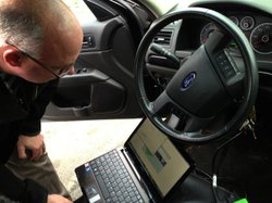 Detective Dave Wells plugs his laptop into a car&#39;s event data recorder. A large portion of new cars are equipped with the device, and the government is considering making them mandatory in all vehicles. But some say there should be an &quot;off&quot; option.