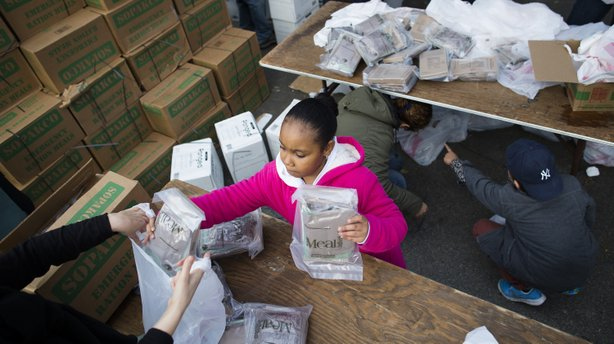 A young woman helps bag ready-to-eat meals for distribution to the residents of the Lower East Side who remain without power due to Superstorm Sandy on Friday.