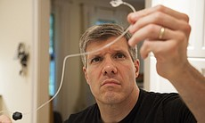 Ed tests tubing for his son's insulin pump. (40062)