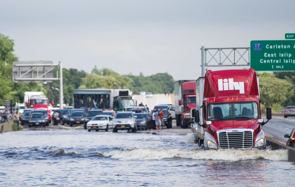 A trailer truck drives through a flooded Sunrise Highway ...