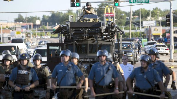 Riot police stand guard as demonstrators protest the shooting death of teenag...