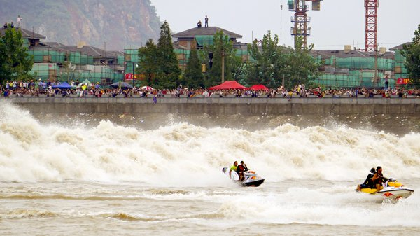 Surfers race in front of the Qiantang Tidal Bore. The wav...