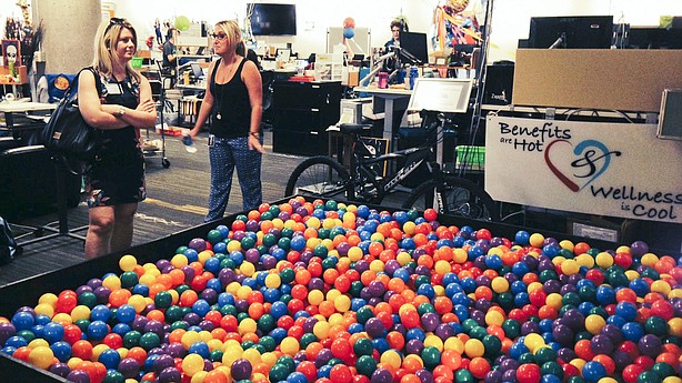 Zappos.com tour guide Erika Newman (right) shows off the ball pit in the human resources department of the company's Las Vegas headquarters. Zappos has eliminated its managers and embraced a system of self-governance known as a holacracy.