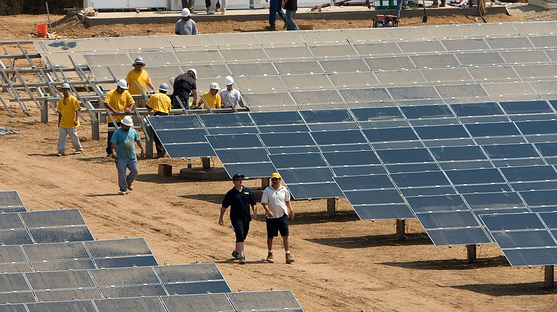 Workers install a solar farm outside Sacramento, Calif. The state aims to att...