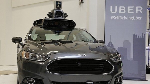 A self-driving Ford Fusion Hybrid Uber is displayed at th...