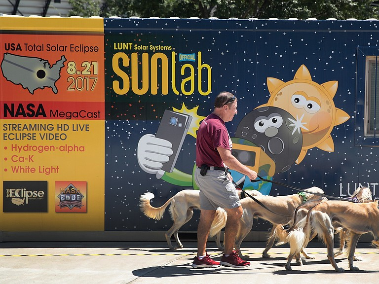 Jim Blair walks Saluki dogs past a solar eclipse exhibit on the campus of Southern Illinois University in Carbondale, Illinois. With approximately 2 minutes 40 seconds of totality the area in Southern Illinois will experience the longest duration of totality during the eclipse on August 21.