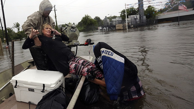 Rhonda Worthington is lifted into a boat while on her cellphone with a 911 di...