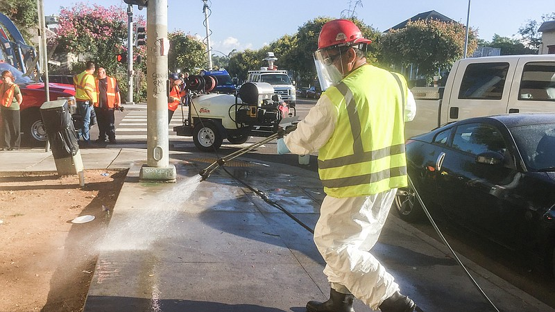 City workers wash down streets and sidewalks Monday in an effort to control a...
