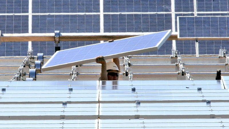 A solar energy panel is carried to be placed in a solar energy field at the S...