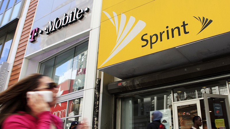 A woman using a cell phone walks past T-Mobile and Sprint stores in 2010.