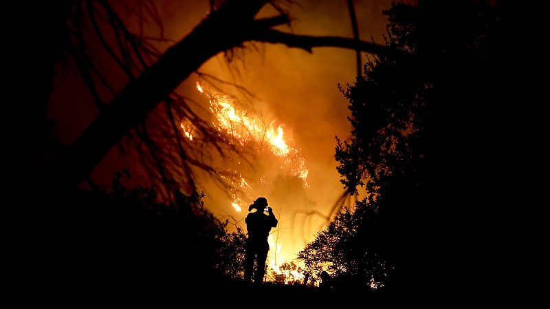 A firefighter snaps a quick picture amid efforts to contain the Thomas Fire i...