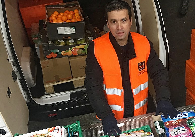 Djerbrani checks a selection of food to be donated from a French grocery store.