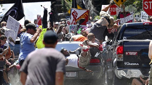 People fly into the air as a vehicle drives into a group of protesters demons...