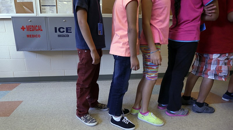 Detained immigrant children line up in the cafeteria at a temporary home for ...