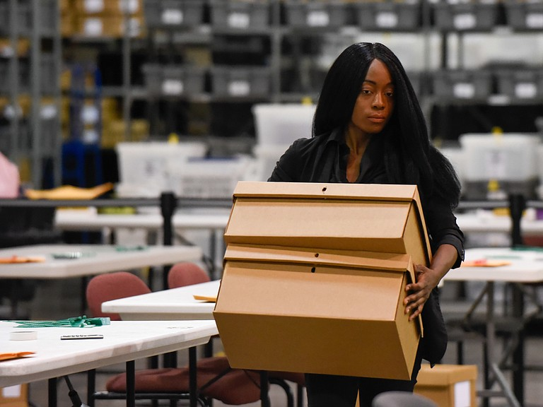 A woman sets up tables for hand counting ballots on Thursday in Palm Beach County.