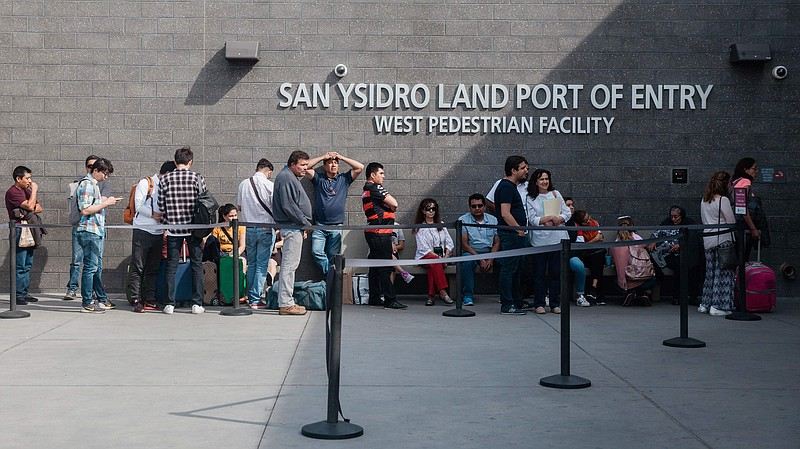 People wait in line outside the San Ysidro Port of Entry, between Tijuana, Me...