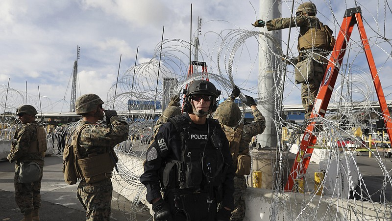 Troops set up concertina wire as a Customs and Border Protection agent stands...