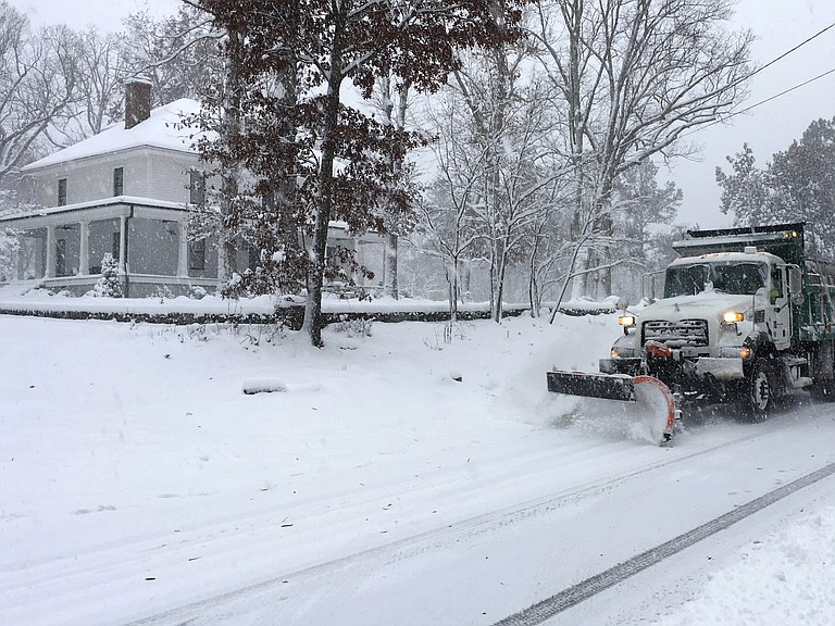 """A snow plow moves on a snowy Durham, N.C., street on Sunday. Weather Prediction Center forecaster David Roth told NPR this could be a """"historic storm"""" for southwest Virginia and western North Carolina."""