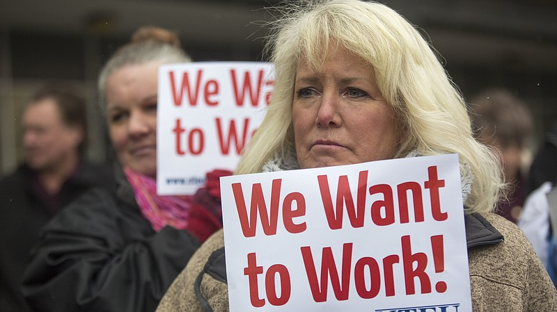 IRS employee Pam Crosbie and others hold signs protesting the government shut...