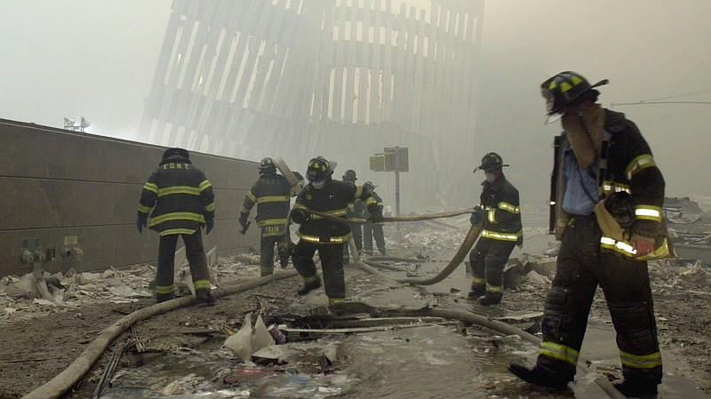 Firefighters work at Ground Zero, the site of the World Trade Center attacks,...