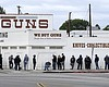 People wait in a line to enter a gun store in C...